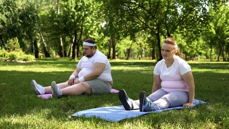 Coppie obese che riposano dopo l'addestramento duro, mancanza di motivazione, perdita di peso immagine stock libera da diritti