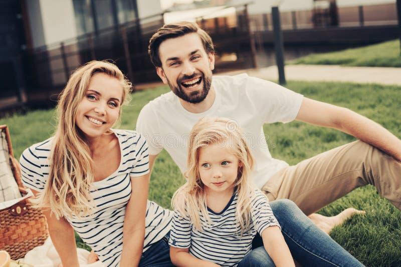 Coppie ottimiste e figlia felice che si rilassano fuori immagine stock libera da diritti