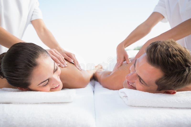 Coppie pacifiche che godono del poolside di massaggio delle coppie fotografie stock libere da diritti