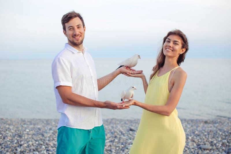 Coppie in parco che gioca con i piccioni locali, divertiresi dei turisti fotografia stock libera da diritti