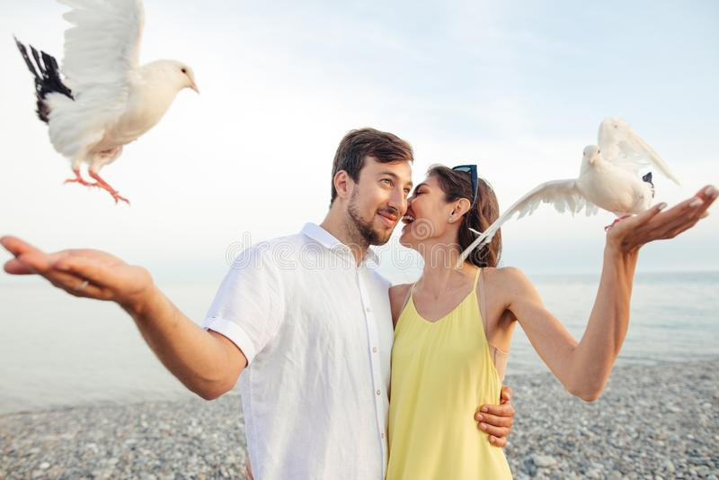 Coppie in parco che gioca con i piccioni locali, divertiresi dei turisti fotografia stock