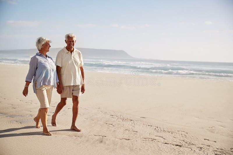 Coppie pensionate anziano che camminano congiuntamente lungo la spiaggia insieme fotografie stock libere da diritti