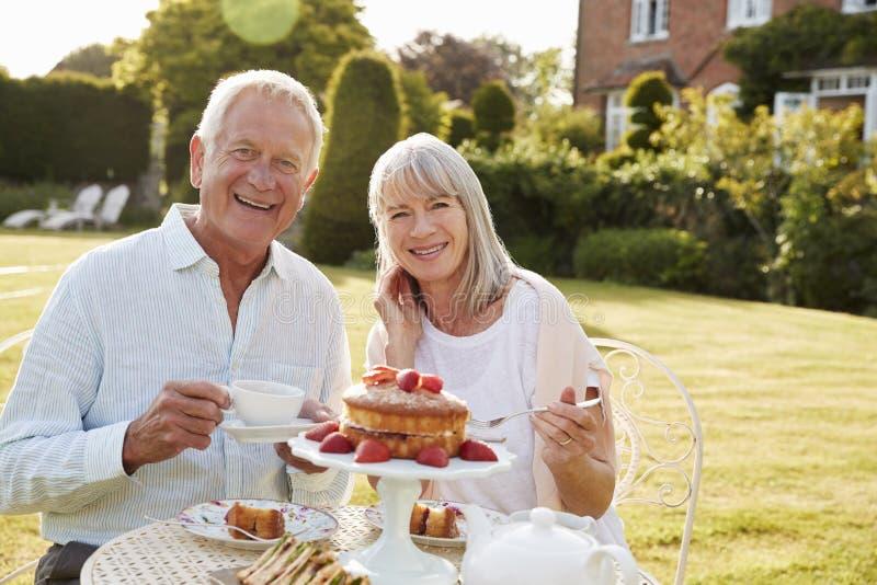 Coppie pensionate che godono del tè di pomeriggio in giardino a casa immagine stock libera da diritti