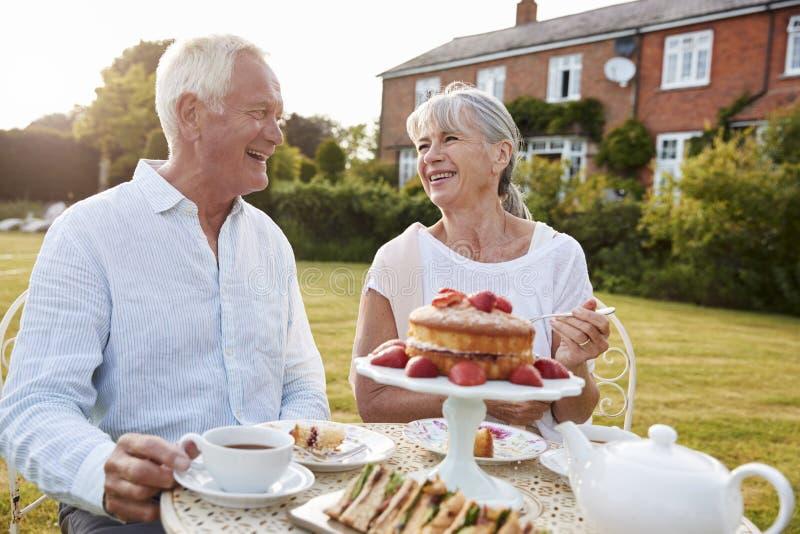 Coppie pensionate che godono del tè di pomeriggio in giardino a casa immagine stock