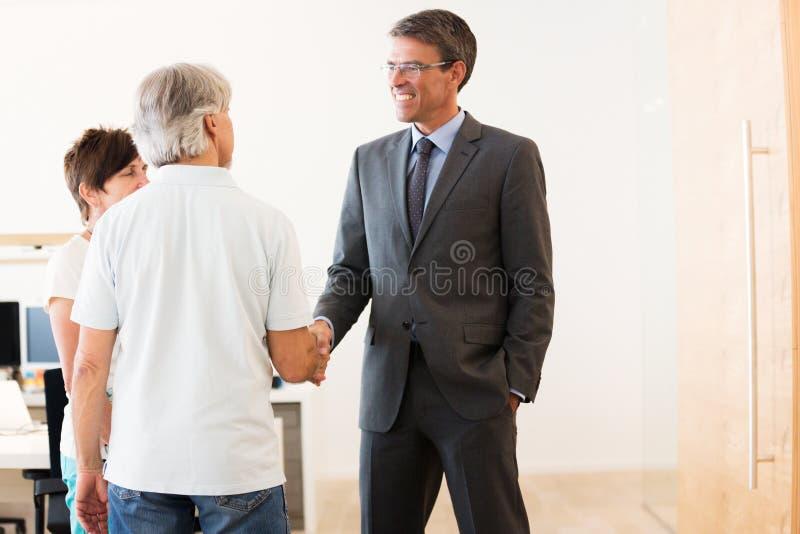 Coppie pensionate che parlano con loro consulente finanziario fotografia stock libera da diritti