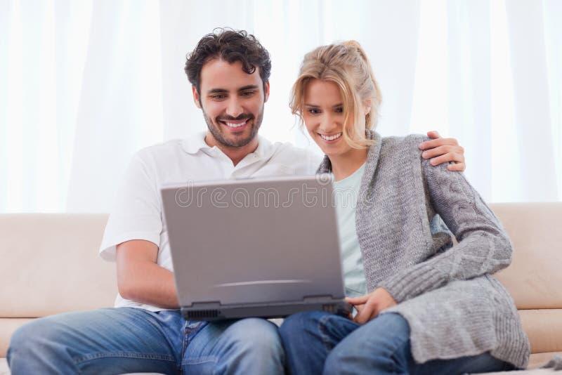 Coppie per mezzo di un computer portatile fotografia stock libera da diritti