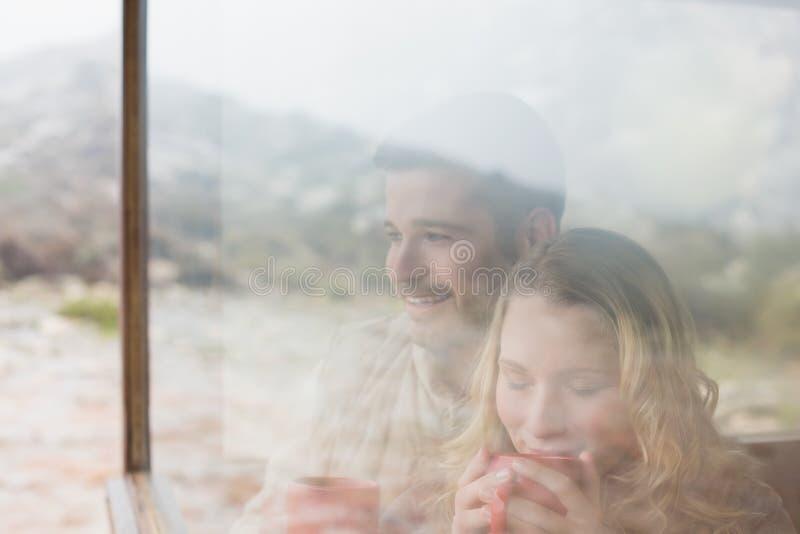 Coppie premurose con le tazze di caffè viste attraverso la finestra di cabina fotografia stock libera da diritti