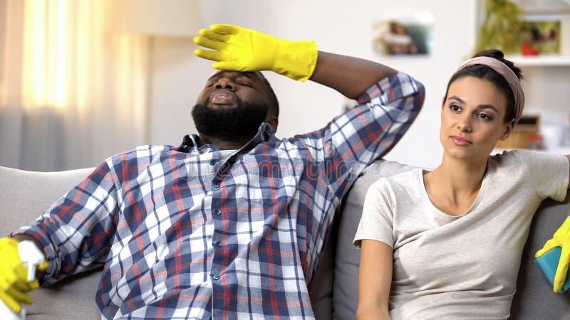 Coppie razza miste stanche in guanti con lo spruzzo della pulitrice che si siede sul sofà, lavoro domestico immagine stock libera da diritti