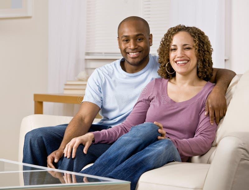 Coppie Relaxed che si siedono sul sofà in salone immagine stock