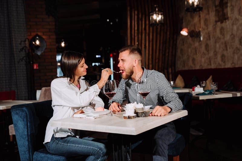 Coppie ricche alla moda che mangiano deserto e vino insieme in un ristorante immagine stock libera da diritti