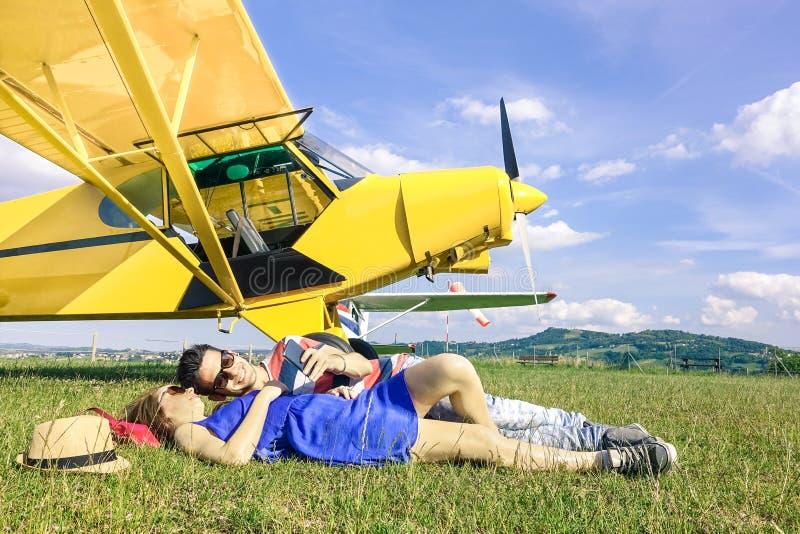 Coppie rilassate degli amanti che hanno un resto al viaggio dell'aeroplano dello statuto immagini stock