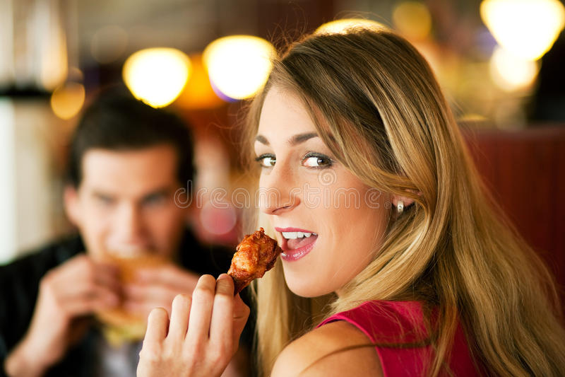Coppie in ristorante che mangia alimenti a rapida preparazione fotografia stock libera da diritti