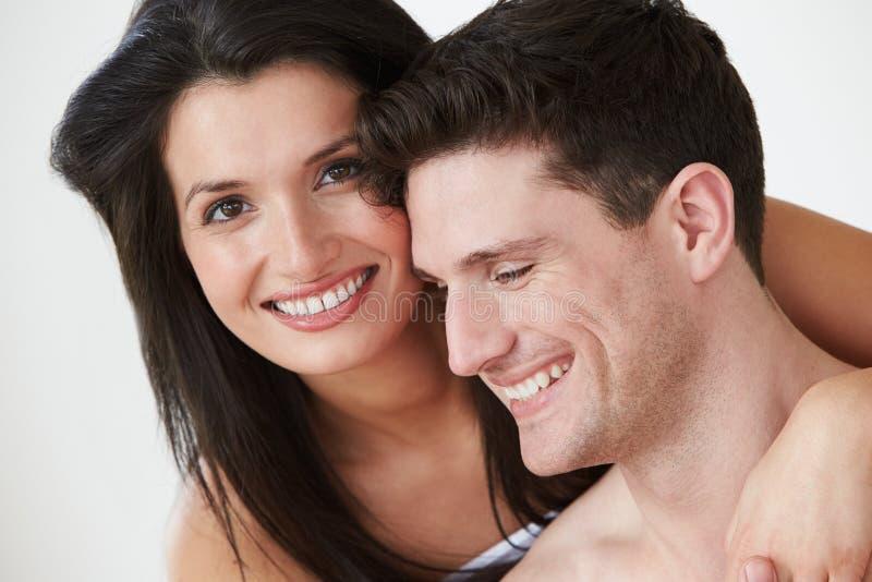 Coppie romantiche che abbracciano contro il fondo bianco dello studio immagine stock