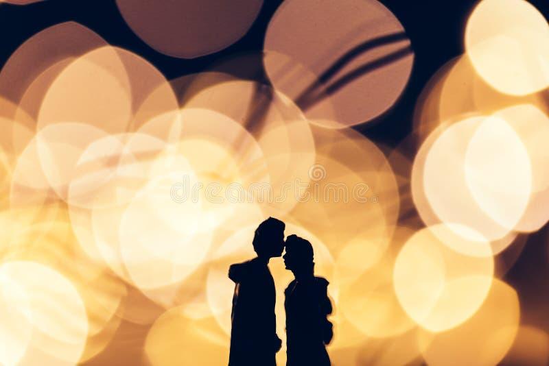 Coppie romantiche che baciano sul fondo illuminato fotografie stock