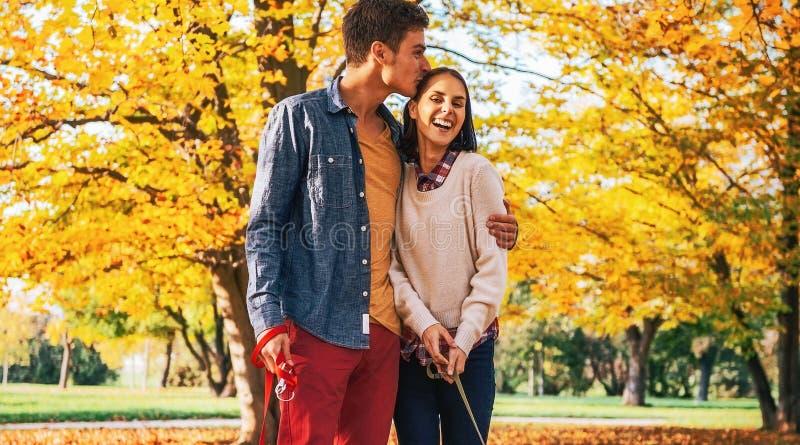 Coppie romantiche che camminano all'aperto nel parco di autunno con i cani immagine stock
