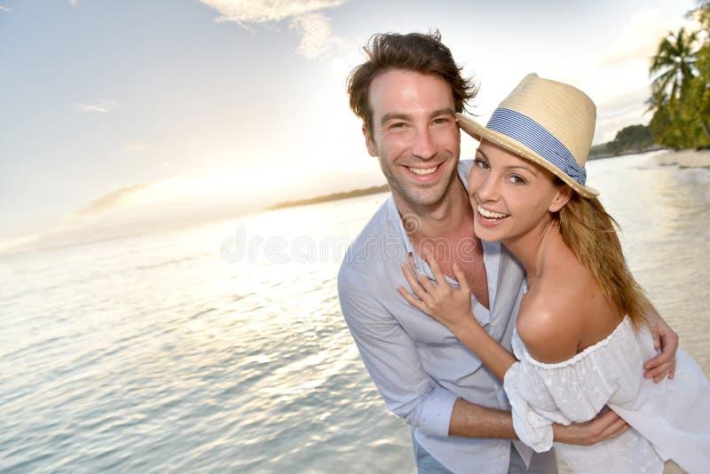 Coppie romantiche che camminano sulla spiaggia fotografia stock libera da diritti