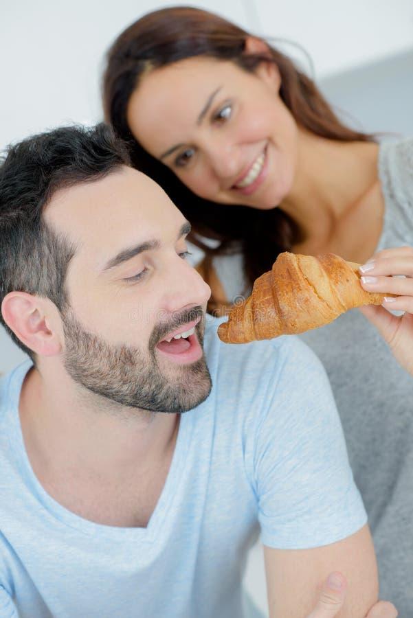 Coppie romantiche che dividono croissant fotografia stock