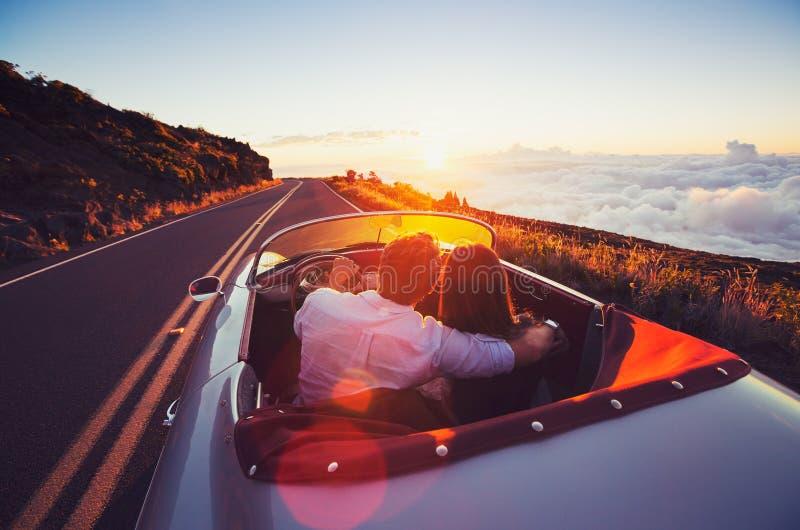 Coppie romantiche che guidano sulla bella strada al tramonto fotografia stock