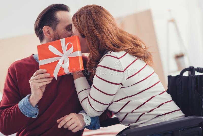 Coppie romantiche che si nascondono dietro il presente e baciare immagini stock libere da diritti