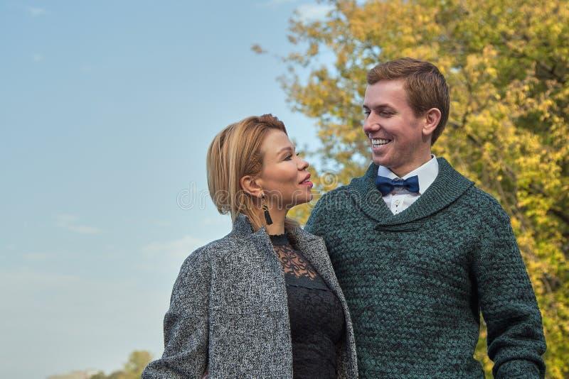 Coppie romantiche che si rilassano nel parco di autunno, stringendo a sé, baciando, godendo dell'aria fresca, bella natura, tempo fotografia stock