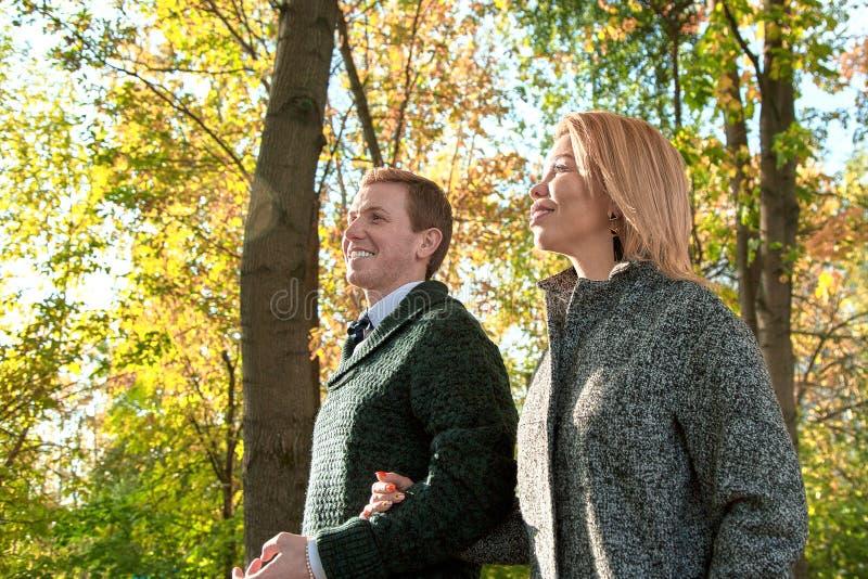 Coppie romantiche che si rilassano nel parco di autunno, stringendo a sé, baciando, godendo dell'aria fresca, bella natura, tempo fotografie stock