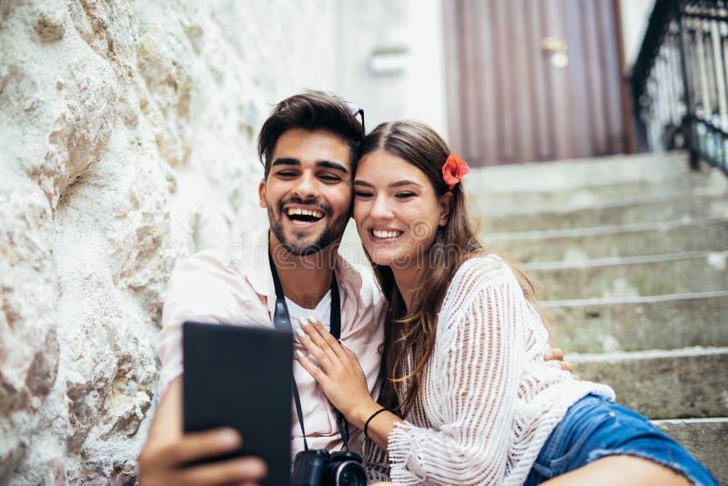 Coppie romantiche che si siedono sulle scale e che esaminano compressa fotografia stock