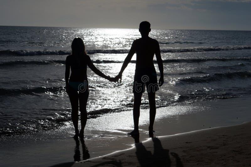 Coppie romantiche che si tengono per mano al tramonto sulla spiaggia immagini stock
