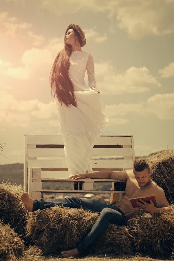 Coppie romantiche che si trovano sul letto L'uomo ha letto il libro su fieno fotografia stock