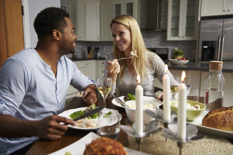 Coppie romantiche della corsa mista che mangiano cena in cucina immagini stock
