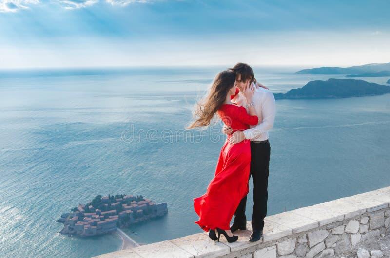 Coppie romantiche di abbraccio accanto al mare blu davanti a Sveti Stef fotografie stock libere da diritti