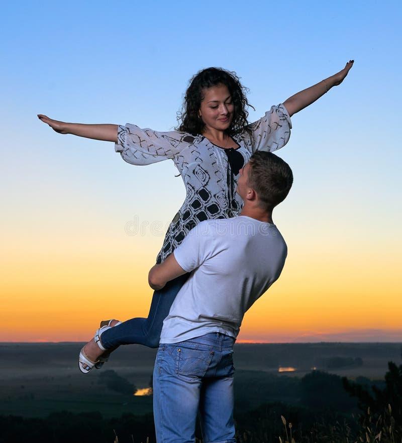 Coppie romantiche divertendosi al tramonto su paesaggio all'aperto e bello e sul cielo giallo luminoso, concetto di tenerezza di  fotografia stock libera da diritti