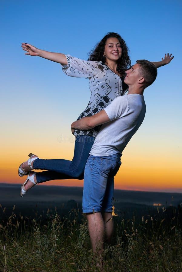Coppie romantiche divertendosi al tramonto su paesaggio all'aperto e bello e sul cielo giallo luminoso, concetto di tenerezza di  immagini stock libere da diritti