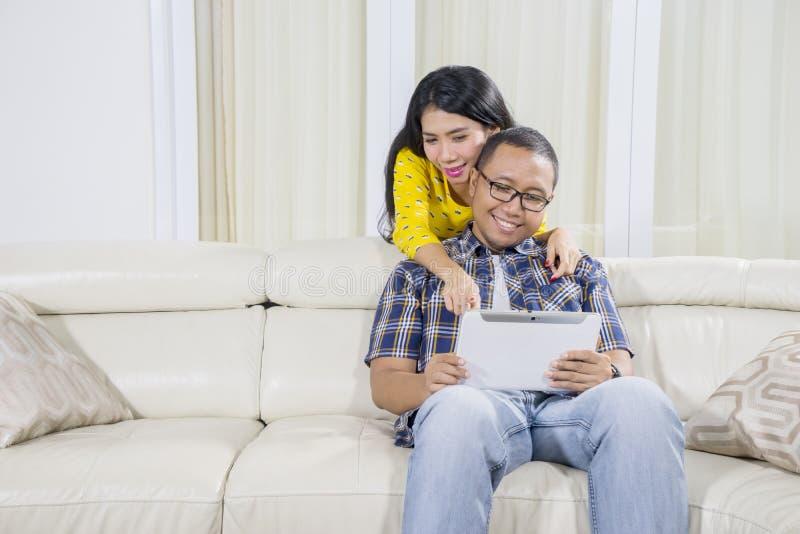 Coppie romantiche facendo uso di una compressa a casa fotografia stock