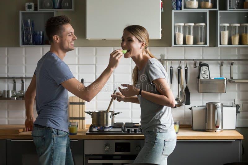 Coppie romantiche felici divertendosi nella cucina che gode preparando f fotografie stock libere da diritti