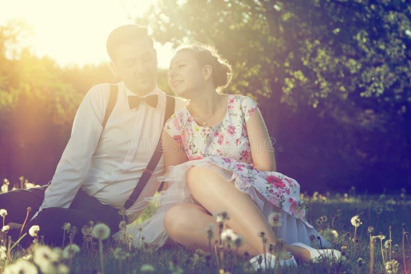 Coppie romantiche nell'amore che flirta sull'erba in parco soleggiato annata immagine stock libera da diritti