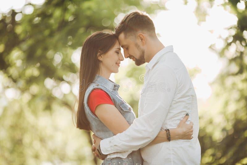 Coppie romantiche nell'amore, sorridente ed abbracciante nel giardino faccia a faccia fotografia stock