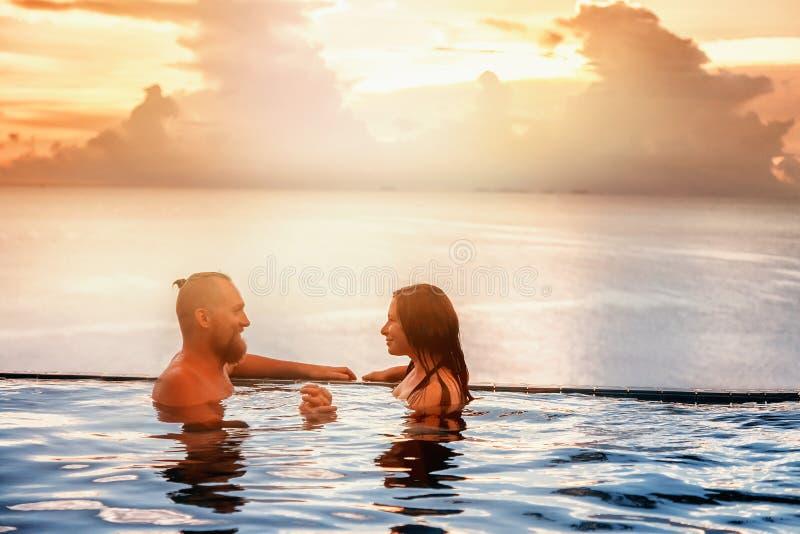 Coppie romantiche nello stagno di infinito al tramonto che trascura la s immagini stock