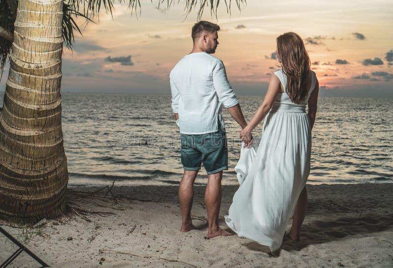 Coppie romantiche sulla spiaggia del Th durante il tramonto fotografia stock libera da diritti