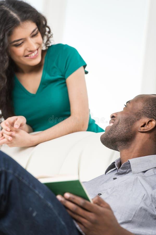 Coppie in salone che parla mentre sedendosi sul sofà fotografie stock