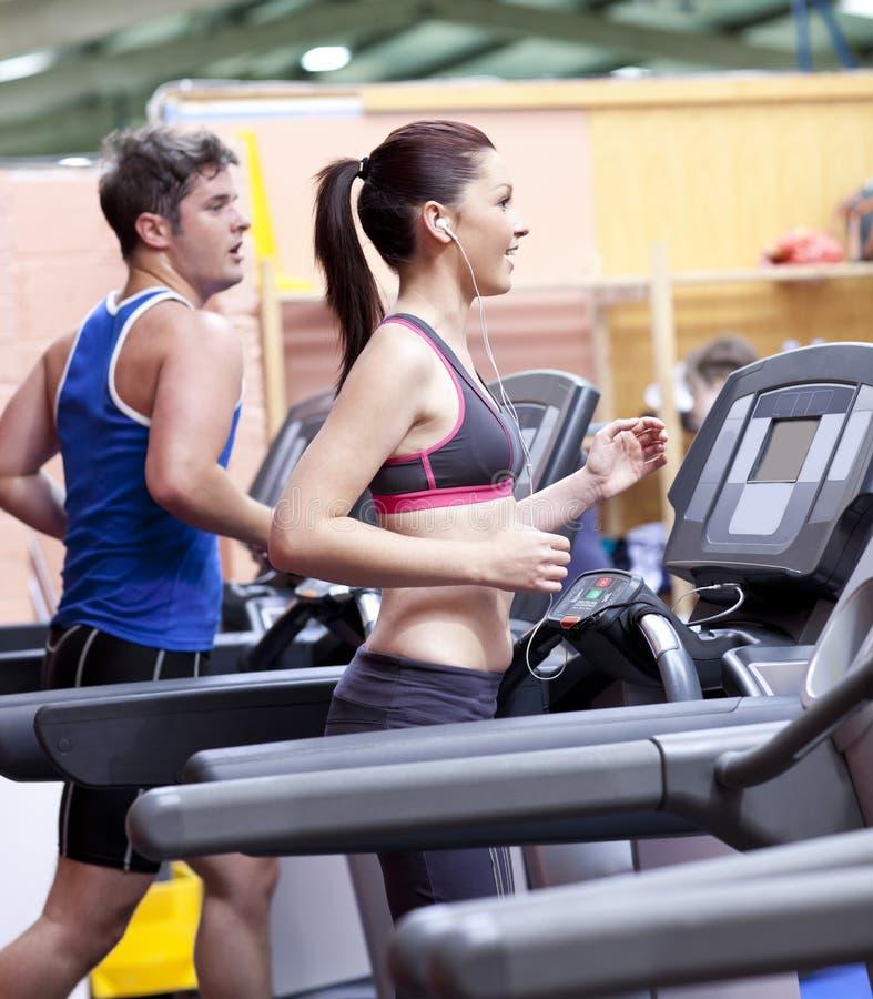 Coppie sane su una pedana mobile in un centro sportivo immagini stock