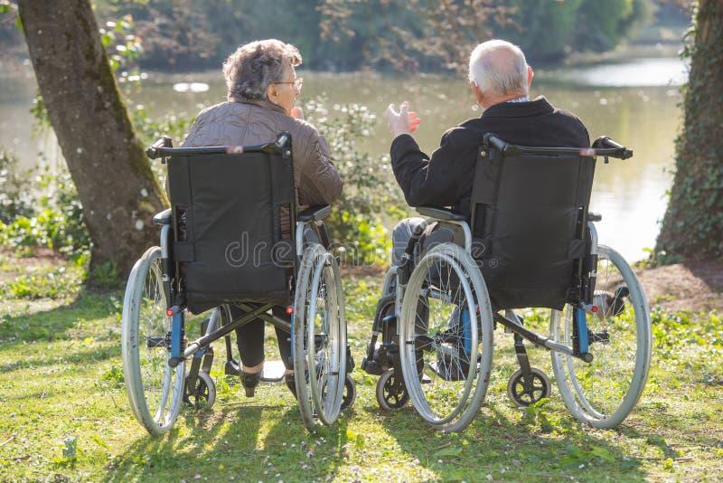 Coppie in sedie a rotelle che esaminano vista fotografia stock
