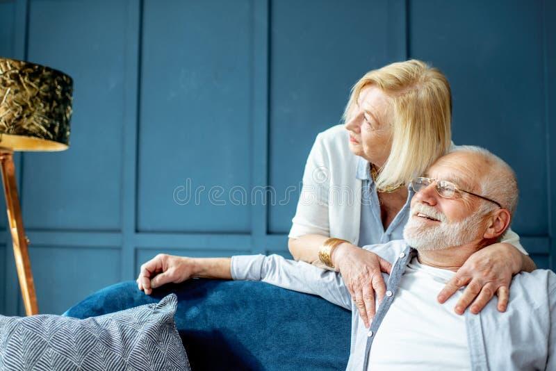 Coppie senior adorabili sullo strato a casa immagini stock libere da diritti