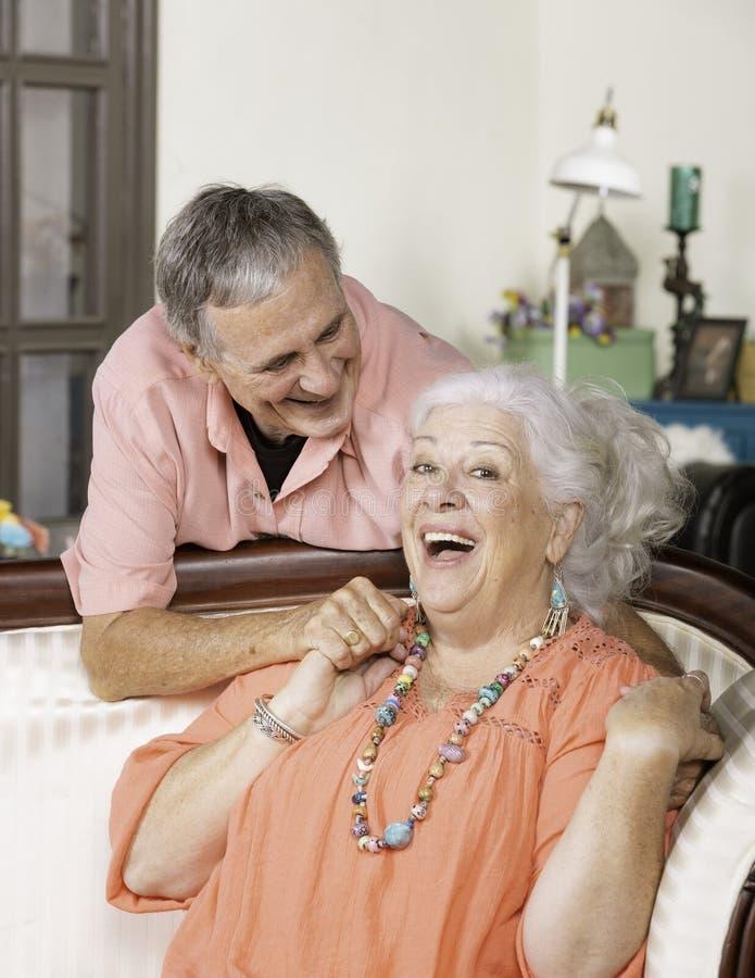Coppie senior affettuose a casa che sorridono immagine stock libera da diritti