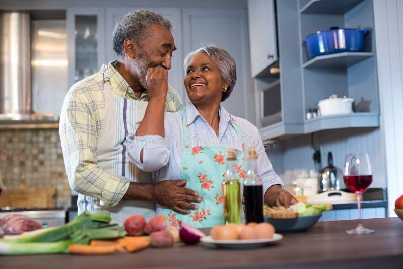 Coppie senior affettuose che preparano alimento immagini stock