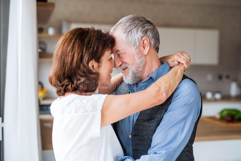 Coppie senior affettuose nell'amore che sta all'interno a casa, abbracciando immagini stock