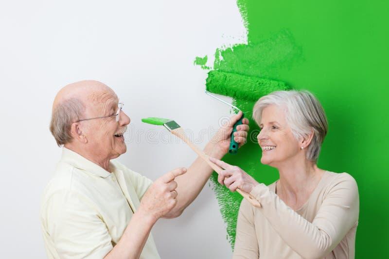 Coppie senior allegre che dipingono il loro verde della casa immagini stock