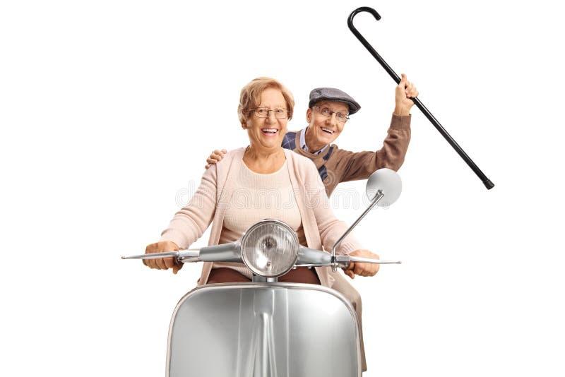 Coppie senior allegre che guidano un motorino d'annata e che tengono una canna su fotografia stock