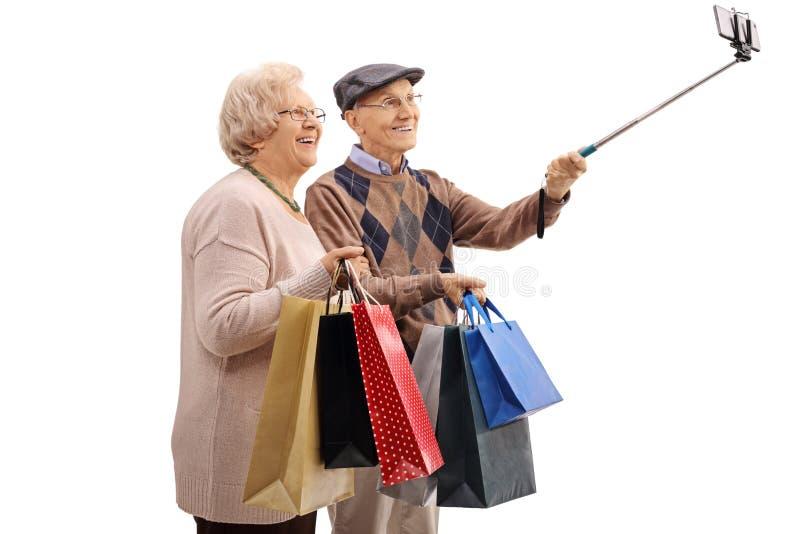 Coppie senior allegre con i sacchetti della spesa che prendono un selfie immagini stock libere da diritti