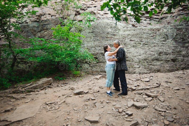 Coppie senior amorose attive che camminano nella bella foresta di estate - concetto attivo di pensionamento fotografie stock