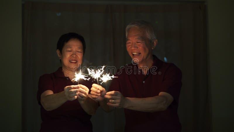 Coppie senior asiatiche che giocano le stelle filante, cracker del fuoco alla notte Concetto che celebra vita immagini stock